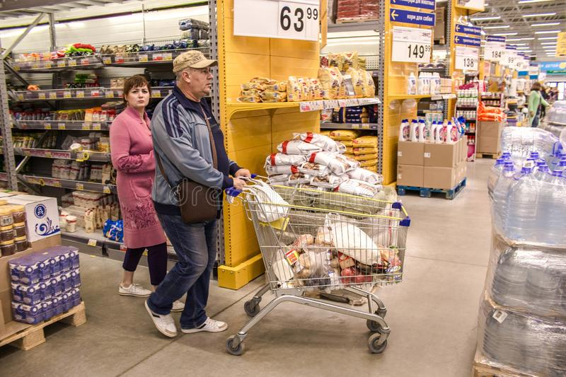 People walk around the Mall and buy food and everyday goods. Shop selling products. People with shopping carts looking. At the shelves and Windows of the market stock image