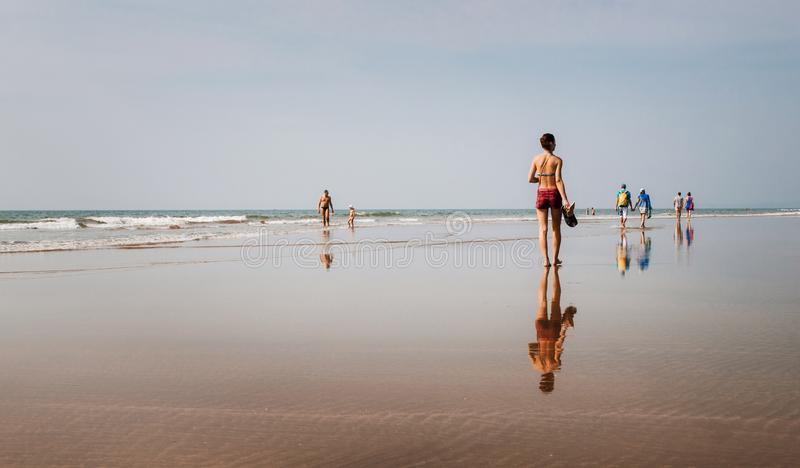 People walk on the beach with mirror reflections, Goa, India stock photography