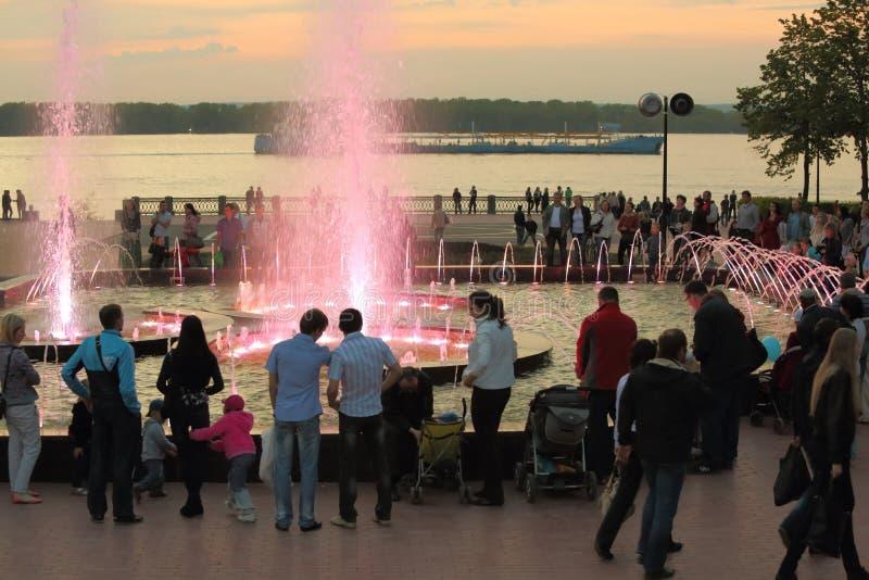 People walk with children near fountain. SAMARA - MAY 5: People walk with children near fountain in evening, on May 5, 2012 in Samara, Russia. Fountain was royalty free stock photography