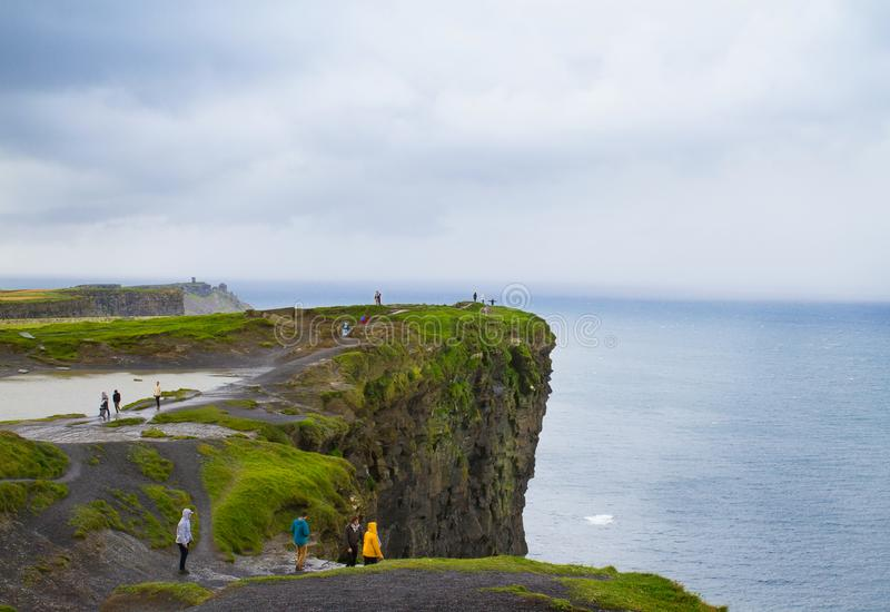 People walk on Cliffs of Moher, west coast of Ireland, County Clare at wild Atlantic ocean, famous tourist attraction. People walk on Cliffs of Moher, west stock photography