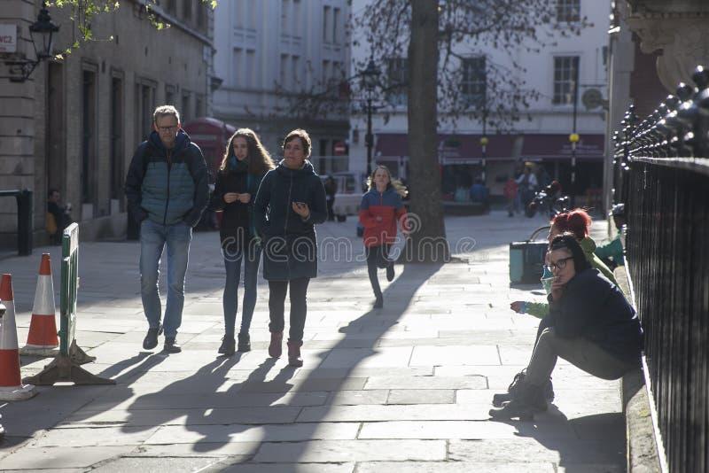 People walk down the street, girls smoke sitting on the fence. LONDON - FEBRUARY 17, 2019: People walk down the street, girls smoke sitting on the fence royalty free stock photo