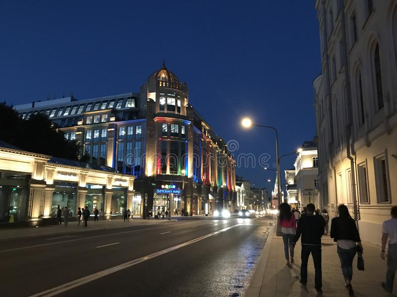 People walk in the evening summer streets of Moscow. Illuminated building of the store `Detsky mir stock photography
