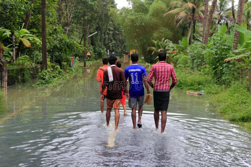 People walk through the flooded roads. Unidentified people walk through the flooded roads on August 16,2018 in Pathanamthitta,Kerala, India. Kerala was badly stock photos