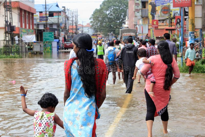 People walk through the flooded roads. Unidentified people walk through the flooded roads on August 16,2018 in Pathanamthitta,Kerala, India. Kerala was badly royalty free stock images