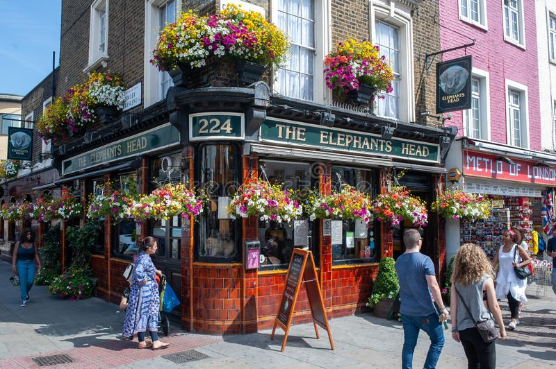 People walk in front of The Elephants Head pub in Camden Town, London. Tourists and locals walk in front of The Elephants Head pub in Camden Town, London on royalty free stock photos
