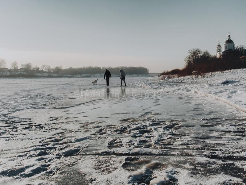 People walk through frozen river. People and a dog walk through frozen river in Polotsk oldest city in Belarus, Belarus stock images