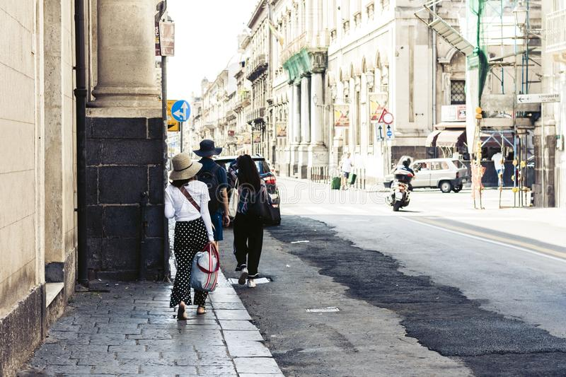 People walk on historical street of Catania, Sicily, Italy.  royalty free stock image
