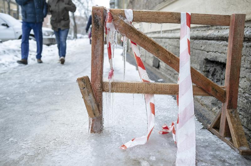 People walk on the icy traumatic sidewalk, which is frozen homemade wooden obstacle, with icicles hanging from it and a protective. People walk on the icy royalty free stock images