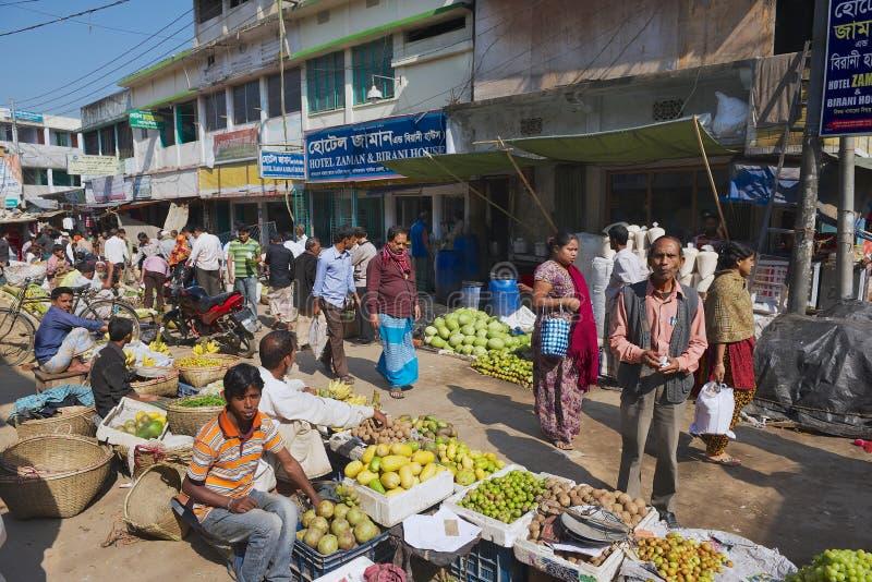 People walk by the local market in Bandarban, Bangladesh. BANDARBAN, BANGLADESH - FEBRUARY 20, 2014: Unidentified people walk by the local market in Bandarban stock image