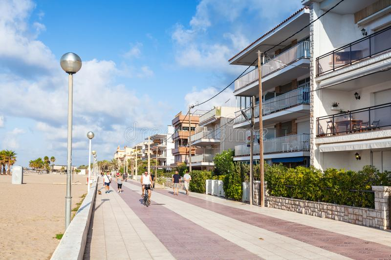 People walk on main street of Calafel, Spain. Calafell, Spain - August 18, 2014: People walk on main coastal street of Calafell town in sunny summer day stock photos
