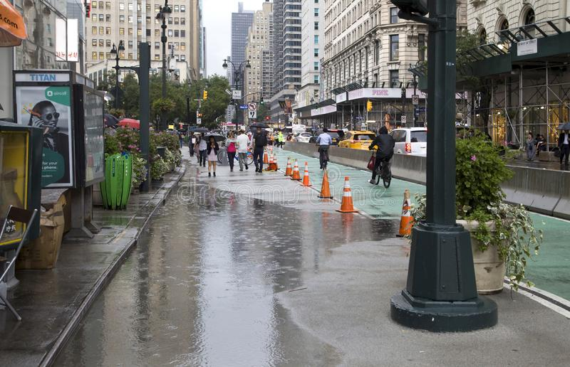 People walk NYC in rain with puddles on streets royalty free stock images