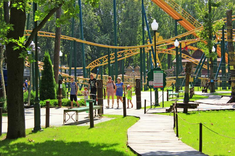 People walk in park with big trees and attractions. Family relaxing in side-show stock photo