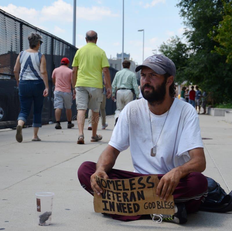 People walk past homeless veteran. DETROIT, MI - JULY 6: Homeless veteran waits as people walk past him as he begs for money in Detroit, MI on July 6, 2014 stock photo