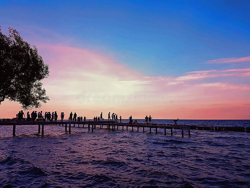 People walk on a pier during sunset royalty free stock photo