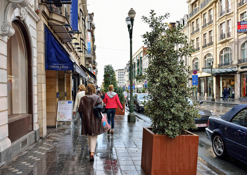 People walk during rain on avenue Louise in Brussels. BRUSSELS, BELGIUM-AUGUST 20, 2014: People walk during rain on avenue Louise. This is mostly expensive royalty free stock photo