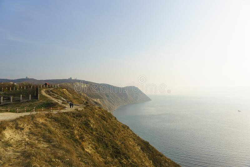 People walk on the road along the steep coast of the Black sea in a foggy autumn day. The surroundings of the resort town of Anapa royalty free stock photography