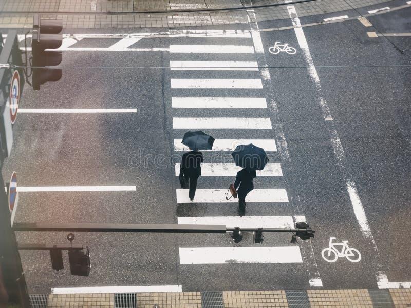 People walk on street Aerial view crosswalk Traffic sign in Raining day. Japan urban lifestyle stock photography