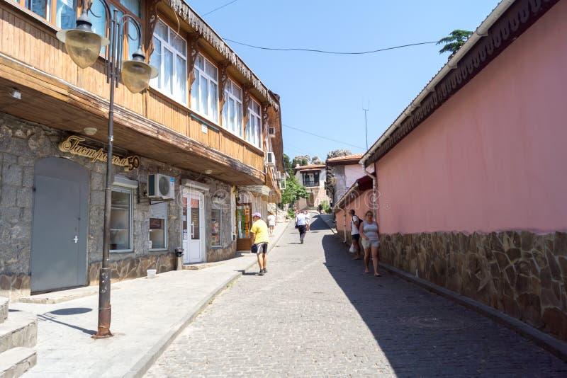 People walk on the street in Gurzuf, inscription-gastronome. Gursuf, Crimea - June 28, 2018: People walk on the street in Gurzuf, inscription-gastronome royalty free stock image