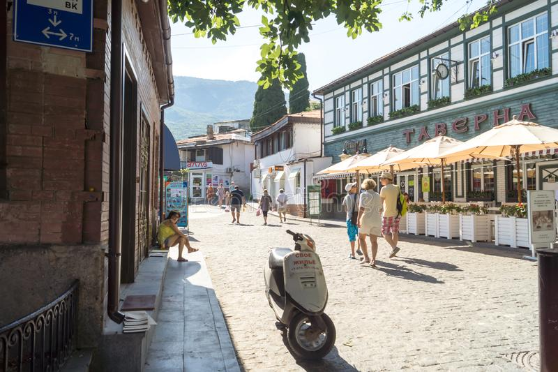 People walk on the street in Gurzuf, the inscription on the moped - their housing, the inscription on the house - tavern stock image