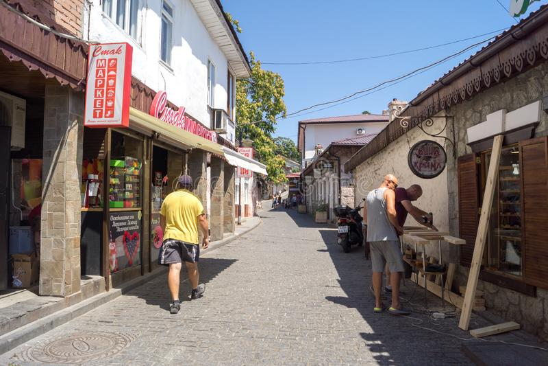 People walk on the street in Gurzuf, inscriptions-relish-market, wine Crimea. Gursuf, Crimea - June 28, 2018: People walk on the street in Gurzuf, inscriptions stock photos
