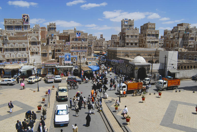 People walk by the street of Sanaa city in Sanaa, Yemen royalty free stock image