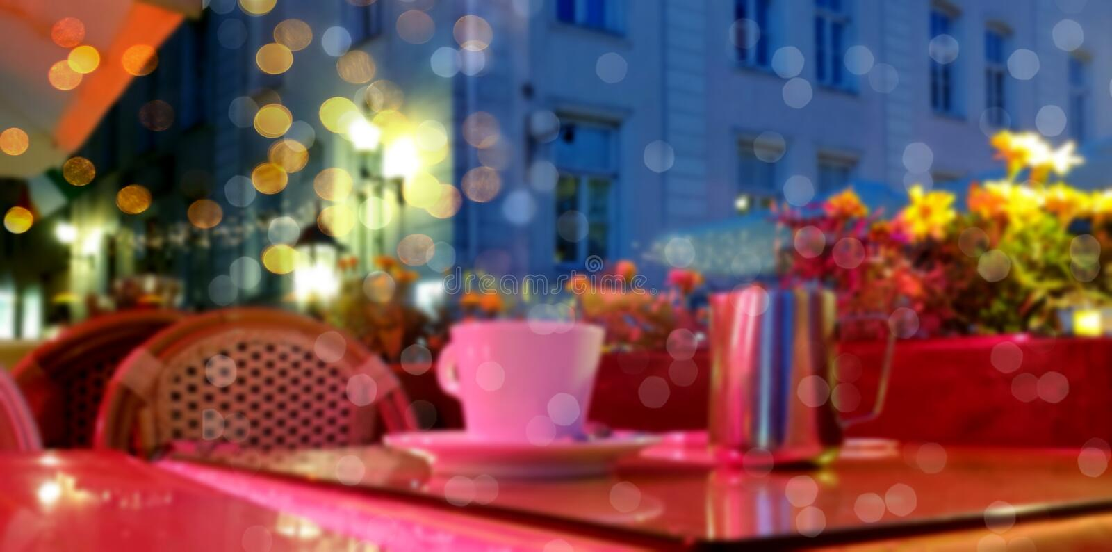 City holiday light blurring Street cafe bokeh g city light evening restaurant table cup of c. People walk under umbrellas rainy evening in Tallinn ,town square stock photos