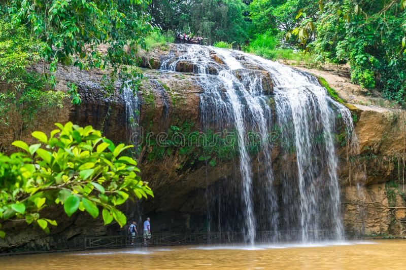 People walk under a waterfall in a tropical forest with green trees in summer stock images