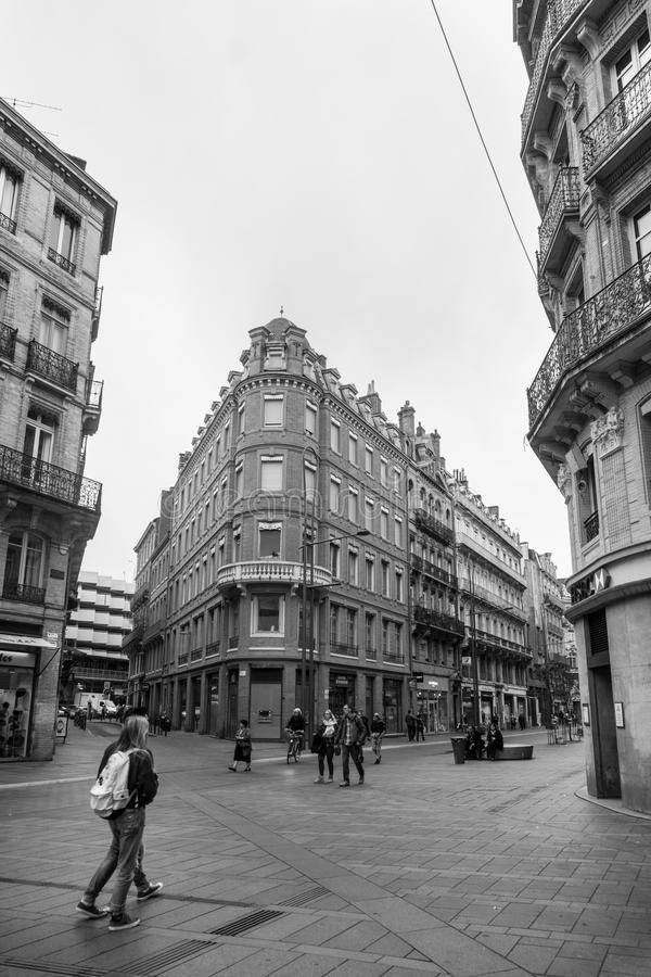 People walkiing through street corner surrounded by buildings of. Toulouse, France - October 25, 2016; People walking through street corner surrounded by stock photography