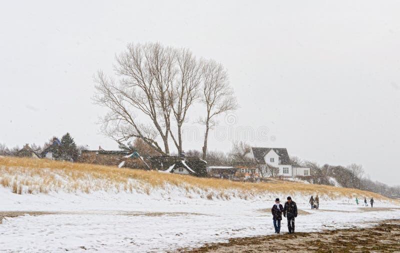 People walking along on Baltic sea beach of village names Ahrenshoop Mecklenburg-Vorpommern, Germany in winter time with snow. Ahrenshoop, Mecklenburg-Vorpommern royalty free stock photo
