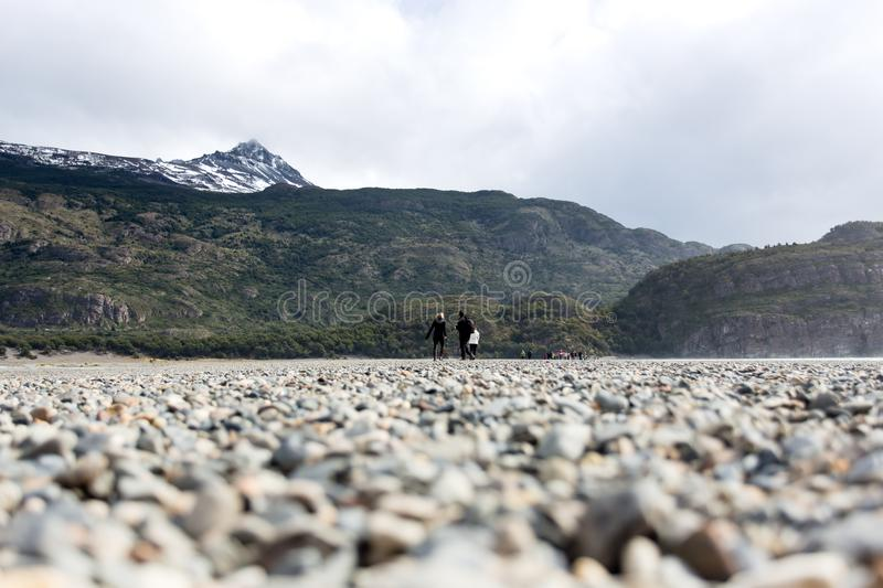 People walking along path during low tide in Glacier Gray, beautiful mountain range with snow in the background. Torres del Paine,. People walking along path stock photos