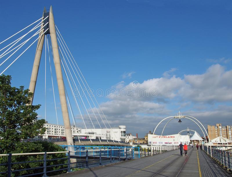 People walking along along the pier in southport merseyside on a bright summer day with the suspension bridge and buildings with a. Southport, merseyside, united stock photos