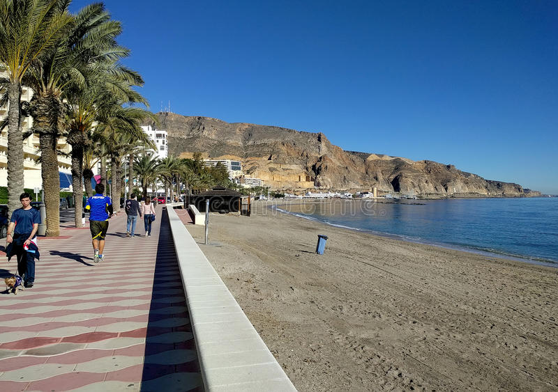 People walking along the seafront promenade of Aguadulce. Spain. Aguadulce, Spain-December 26, 2016: People walking along the seafront promenade of Aguadulce royalty free stock photos