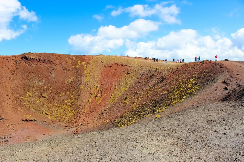 People walking around the colorful crater in Silvestri craters on Mount Etna in Sicily, Italy. The stunning volcanic landscape. Is a popular hiking spot royalty free stock photography