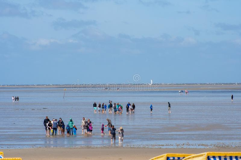 People walking on the beach in Cuxhaven at low tide. People in the water on the North Sea stock photos
