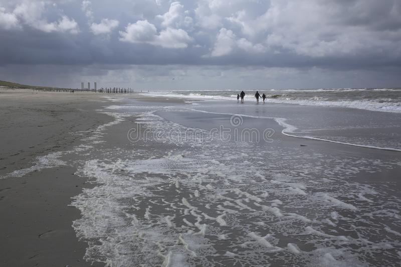 People walking on the beach with stormy weather stock photos