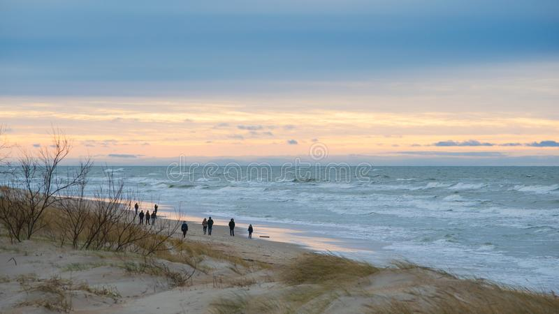 People walking on beach in winter evening in Palanga royalty free stock photos