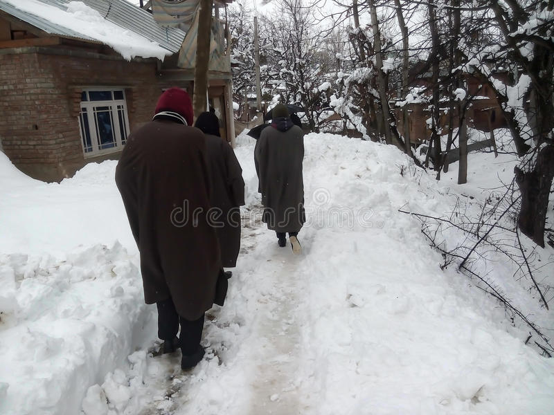 People are walking carefully on snowy path royalty free stock photo
