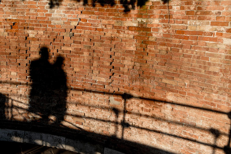 People walking, casting shadows on a wall stock image