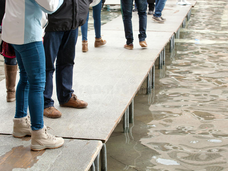 People walking on catwalk in Venice. During the high tide stock photo
