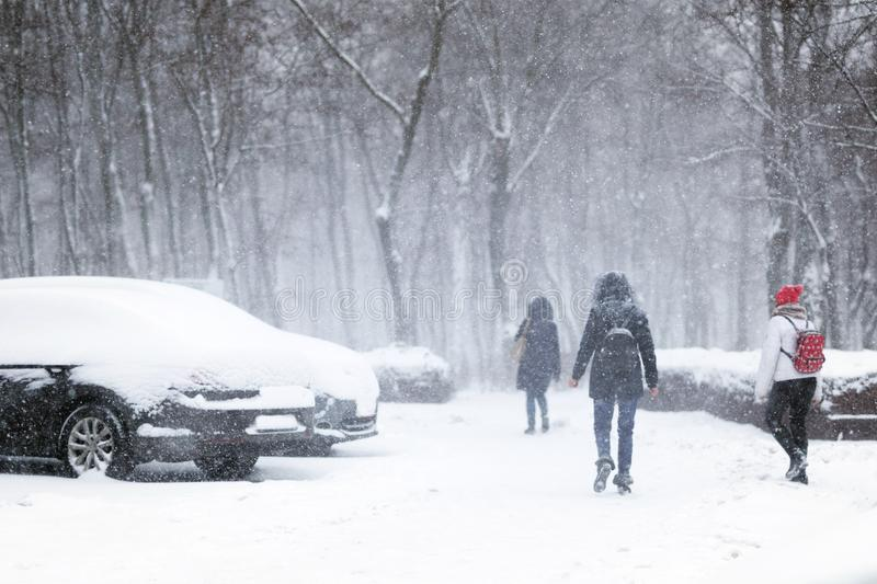 People walking through city street covered with snow during heavy snowfall. Blizzard in town at winter. Natural disasters, snow stock images