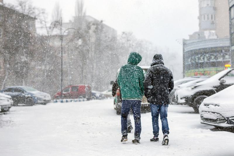 People walking through city street covered with snow during heavy snowfall. Blizzard in town at winter. Natural disasters, snow royalty free stock photography