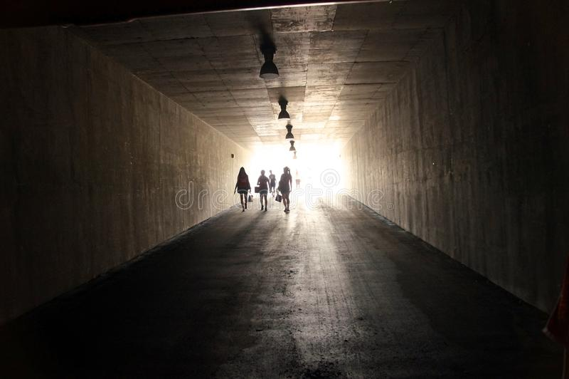 People are walking through dark tunnel stock photos