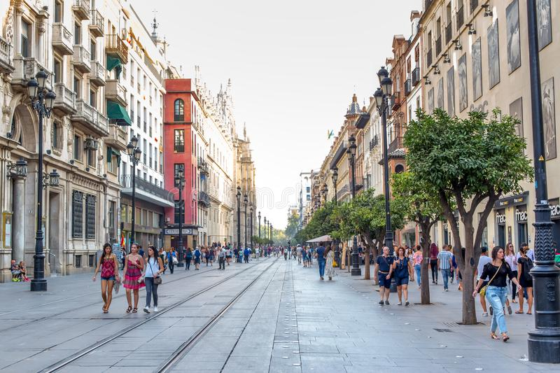 People walking during the day in a pedestrian street near Cathedral in Seville, Spain. Famous landmark. royalty free stock photos