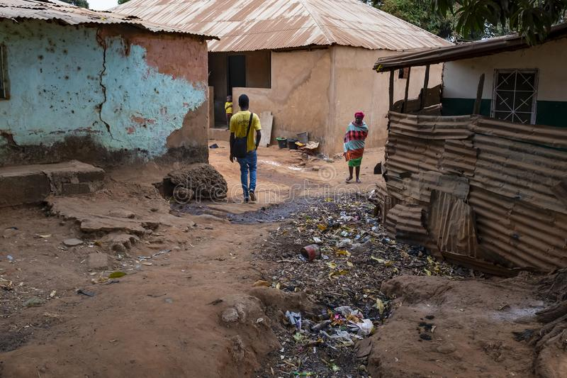 People walking in a dirt street with an open air sewer, at the Missira neighborhood in the city of Bissau. Bissau, Republic of Guinea-Bissau - February 6, 2018 stock image