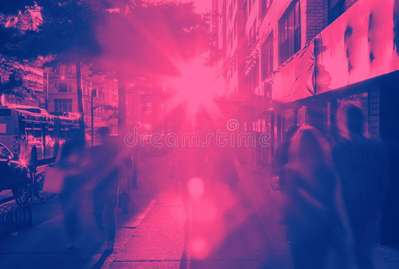 People walking down the sidewalk in New York City in pink and blue royalty free stock photography