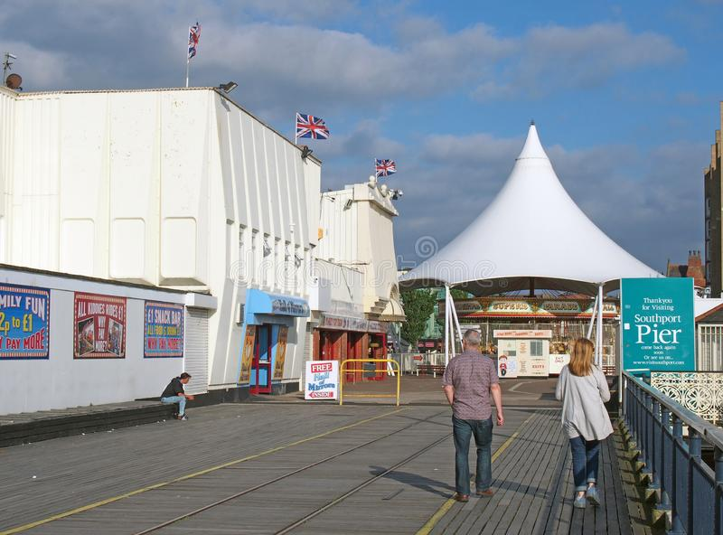 People walking into the entrance to southport pier in merseyside with a carousel and amusement arcade royalty free stock photography