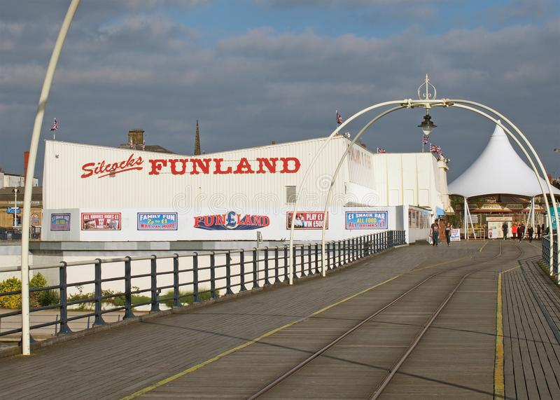 People walking into the entrance to southport pier in merseyside with a carousel and amusement arcade royalty free stock images