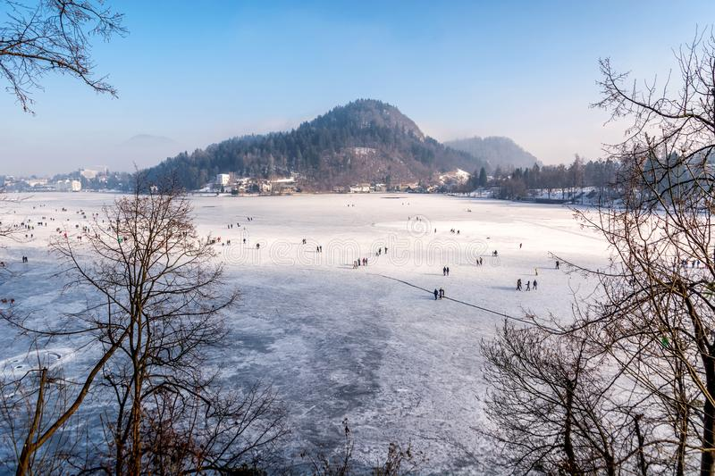 People walking on frozen lake Bled ice towards the island royalty free stock images