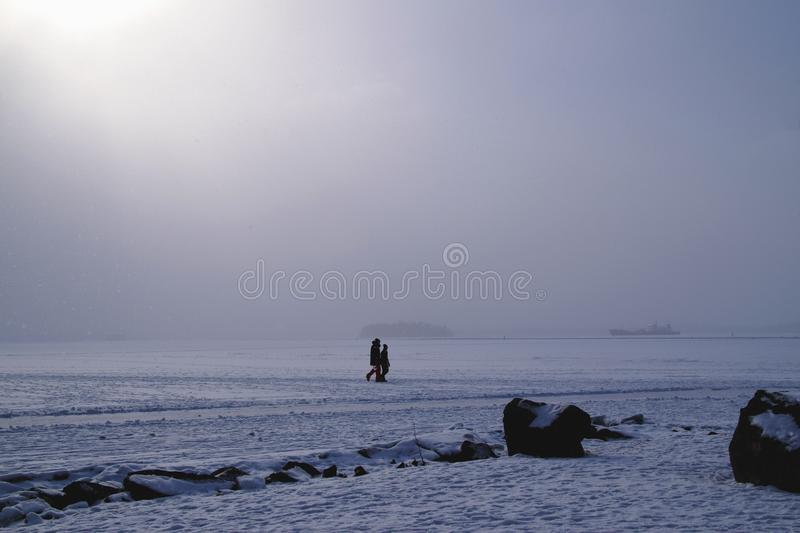 People walking on the frozen lake. Two unrecognizable people going for a walk on the frozen lake while it snows. Far off in the horizon is a ship. Photo taken in royalty free stock images