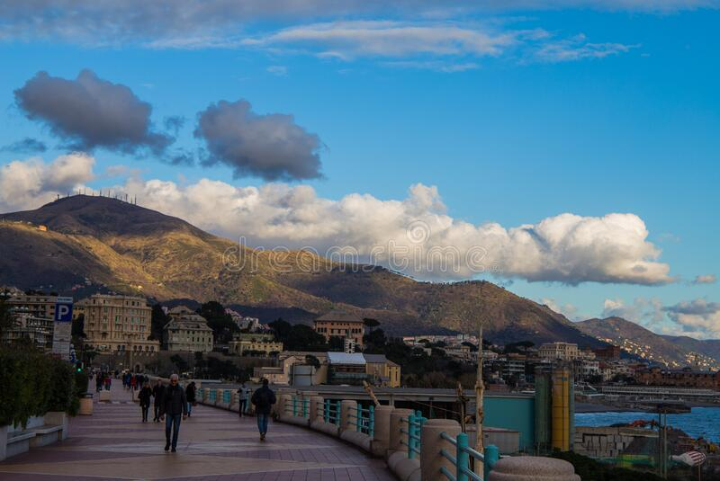 People walking on the Genoa promenade in a sunny day with a sky with clouds stock photo